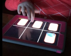 child's hand doing a flick up finger gesture on iPad screen with iPad cover around it