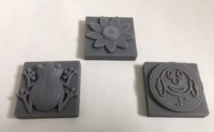 3D printed grid tiles of frog, flower, and Ballyland coin.