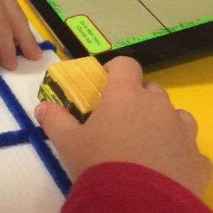 girls hand holding toy car in tactile grd made of cardboard and wikki stix